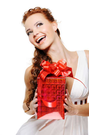 Happy laughing woman holding the present and looking up over white background photo