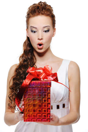 Portrait of an astonishment female holding the box with gift - isolated on white photo