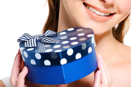 Half smiling face of young female  holding the blue present box photo