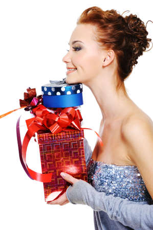 Profile portrait of a pretty young female with a heap christmas present boxes photo