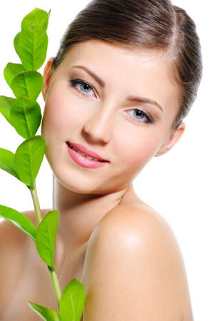 Beautiful smiling female face with a clean healthy skin and plant near her body Stock Photo - 5721758