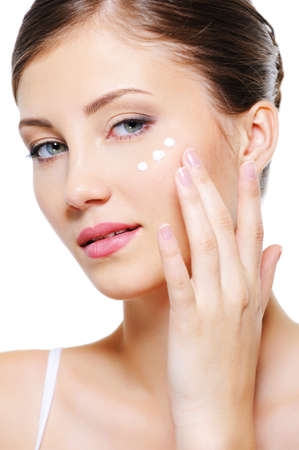 woman face cream: Beauty female applying cosmetic cream on skin around eyes - isolated on whhite  Stock Photo