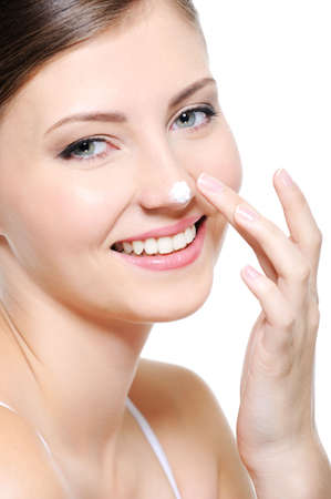 Beauty smiling female face with drop of  cosmetic cream on her nose photo