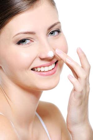 nosa: Piękna kobieta uśmiechnięta twarz z kropli kosmetycznych krem na nosie