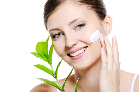 facial cream: Green leaf near beauty woman  applying moisturiser cream on her clean skin of face Stock Photo
