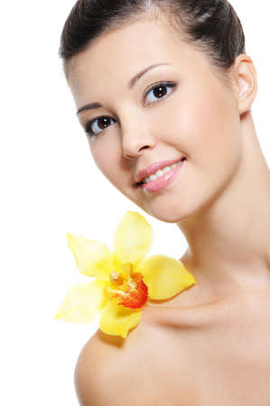 feminity: Beauty happy young asian girl with yllow orchid on her shoulder