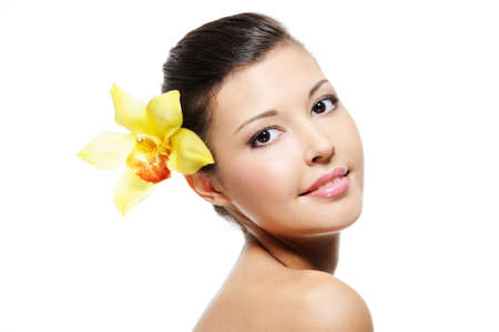 Beauty smiling female face with yellow orchid from her ear - over white background photo