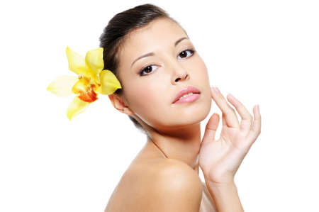 Beauty asian woman with a wellness skin of her face with a yellow orchid from her ear photo