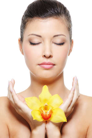 Close-up face of a beauty asian woman relaxation with flower in hands photo