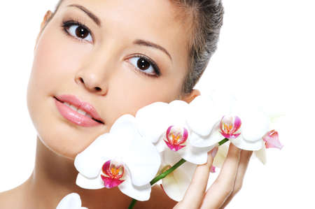 Close-up portrait of an asian beauty girl with flower near her face - skincare treatment photo