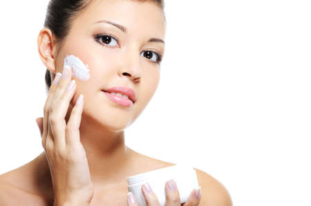eyes hazel: Beauty asian female skincare of her face by applying cosmetic cream on her cheek