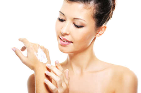 cosmetic cream: Beauty smiling female  applying cosmetic cream on her hands - over white background
