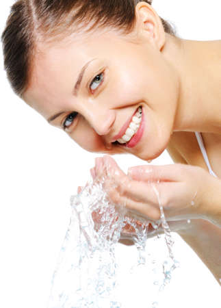 hand on face: Happy beautiful woman wash her face with pure water - isolated Stock Photo