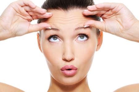 Close-up vrouwelijk gezicht met een grote rimpels op haar voorhoofd - op wit wordt geïsoleerd