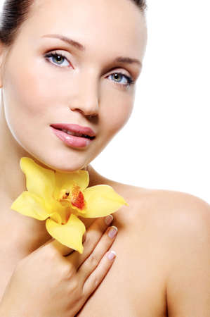Serene face of young beauty woman with a yelow flower  - isolated on white Stock Photo - 5769521