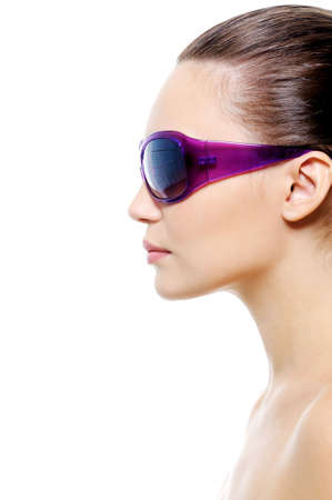 Profile portrait of an young female face in violet sunglasses