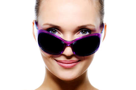 Front view portrait of beautiful smiling woman face in dark violet sunglasses - isolated on white photo