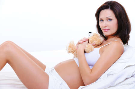 Pretty smiling young pregnant female embrace the teddy toy  Stock Photo - 5790026