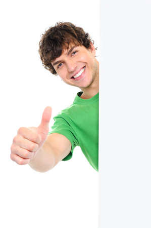 Happy handsome man showing thumbs up look out from white blank banner photo