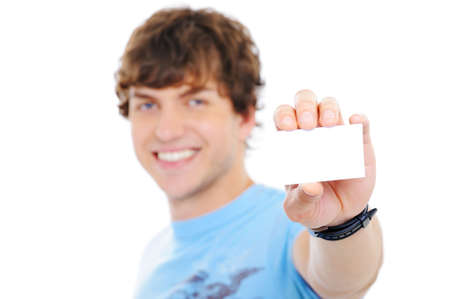 holding head: Handsome happy guy showing the blank card on foreground - soft focus