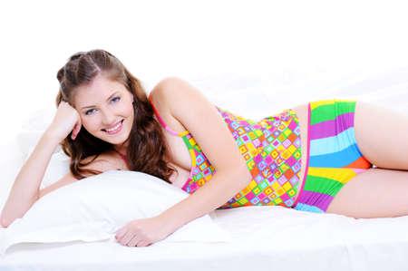 girl lying down: Cute joven sonriente acostado en la cama en ropa de dormir abigarrada - aislado  Foto de archivo
