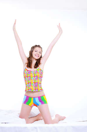 Young pretty girl stretch oneself after wake-up - over white background photo