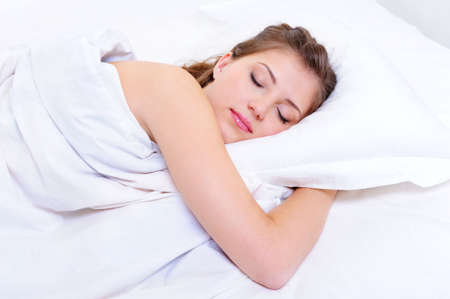 sleeping woman: Beautiful young adult woman sleep in her bedroom Stock Photo