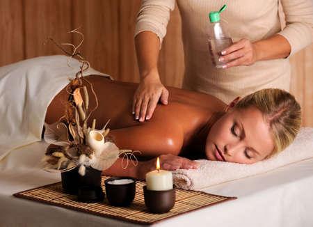 massage oil: masseur professionnel de l'application d'huile de massage sur le dos des femmes dans le salon de beaut� Banque d'images
