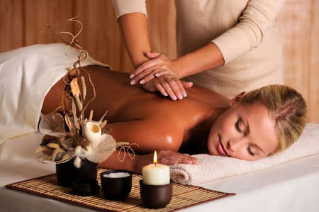 salon: professional masseur doing massage of female back in the beauty salon