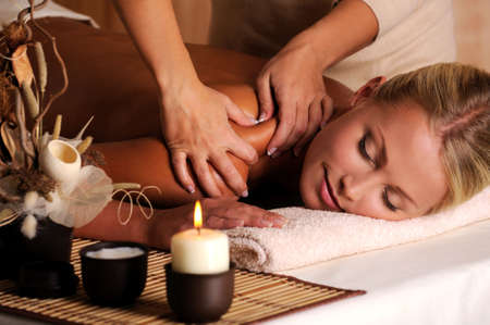 Massage therapy: Masseur doing massage on female shoulder in the beauty salon