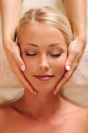 beauty salon face: Close-up portrait of a pretty female face getting relaxation massage of head
