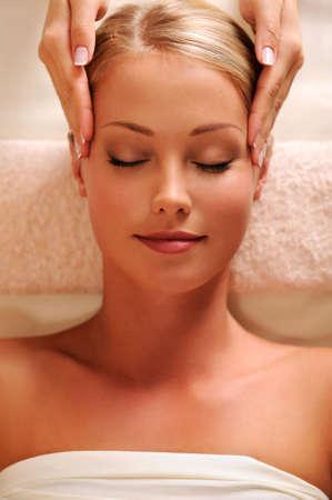 Masseur doen massaging tempels voor jonge prachtige vrouw - hoge hoek weergave
