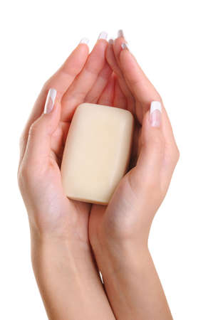 Beautiful female hands hold the white soap - over white background photo