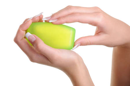 Well-groomed human female hands holding the green soap photo