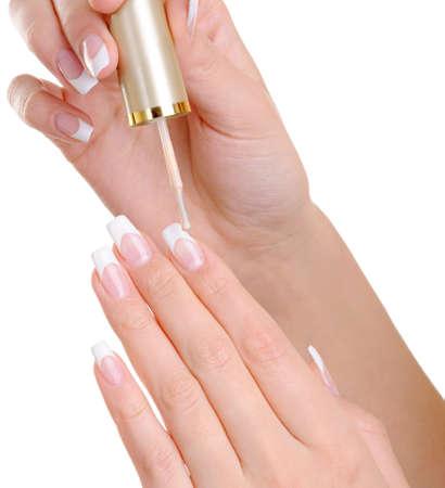 vanish: macro shot of female hands  applying clear nail vanish on her fingernails -