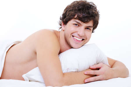 Portrait of a happy smiling young beautiful man lying in the bed photo