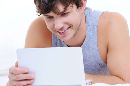Portrait of a happy young guy with laptop photo