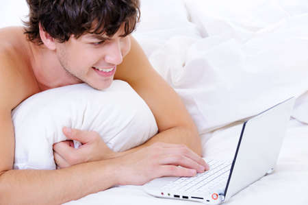 Portrait of a smiling man with laptop lying in the bed photo