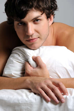 handsome pretty young man lying in bed with pillow Stock Photo - 5840510