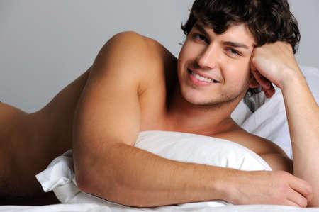 nudo maschile: Bello sexy sorridente giovane sdraiato a letto con cuscino Archivio Fotografico