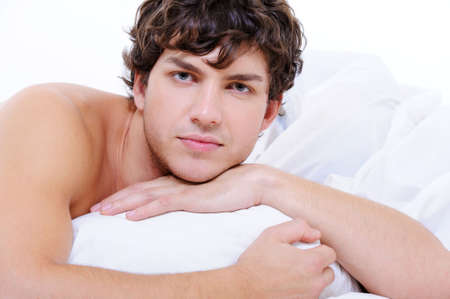 Portrait of calm man with a handsome face lying in bed with pillow photo