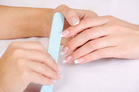 manicurist: Manicurist doing the  polishing female fingernails with the french manicure Stock Photo