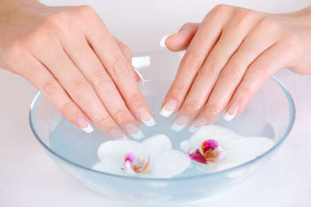 female putting her beautiful fingers into the bowl with water - spa treatment concept photo