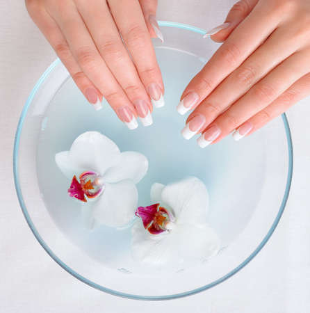 Beautiful female hands with french manicure preparing for getting spa procedure   photo