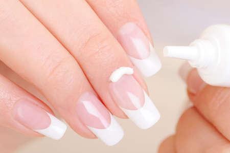 укрепление: Woman caring of her finger applying the moisturizing cosmetic cream on fingernail Фото со стока