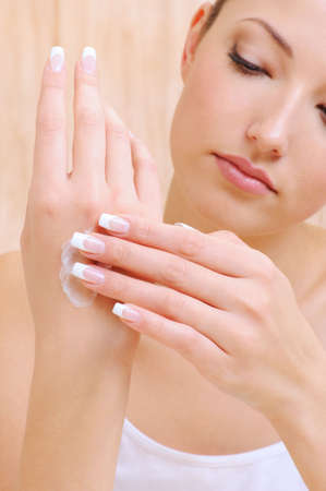 Young beautiful Woman applying cosmetic cream on hands photo