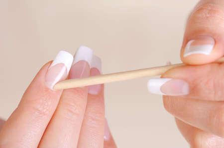 soft focus: Mujer cut�cula limpieza en manos con un palo de cosm�tico - macro dispar� y foco suave