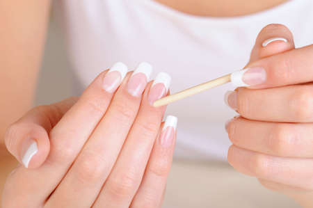 Female hand  with a cosmetic stick for  cleaning cuticle - macro shot photo