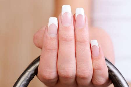 macro shot of a beautiful elegant female fingers with french manicure photo