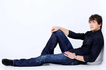 poses de modelos: Full-lenght retrato de un hombre sexy y apuesto mentir plantean en el estudio de